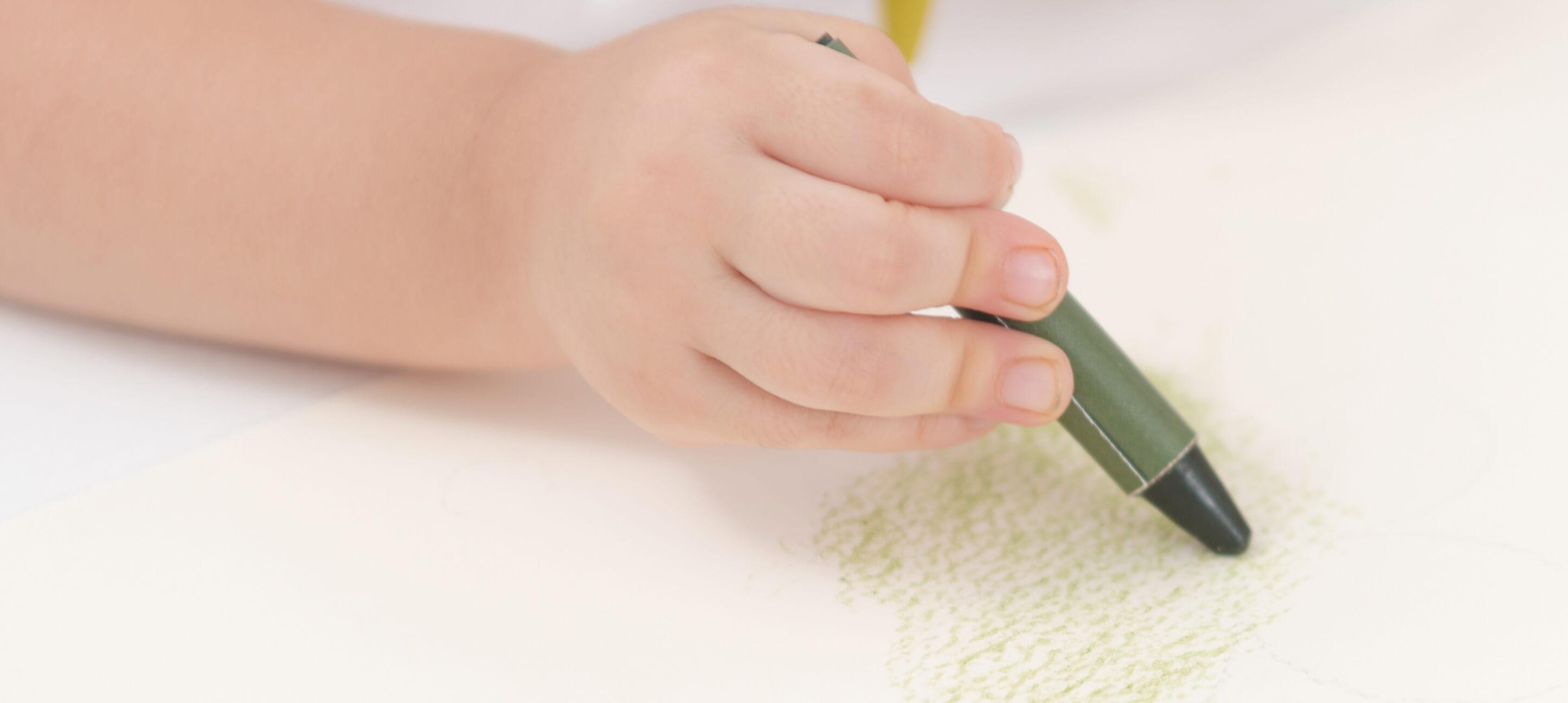 おやさいクレヨンでお絵描きをする子どもの手のスライド画像